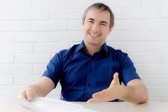 Myślący biznesmen dotyka jego kierowniczego mienia przy stołem dokumentu obsiadanie mężczyzna w biznesu odzieżowym obsiadaniu prz zdjęcia royalty free