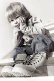Myślący chłopiec obsiadanie na schodkach Zdjęcia Royalty Free