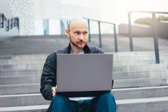 Myślący dorosły pomyślny łysy brodaty mężczyzna w czarnej kurtce używać laptop w schodkach przy miastem obrazy stock