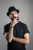 Myślący modniś jest ubranym czarną koszulki i kapeluszu uderzania brodę patrzeje daleko od zdjęcia royalty free