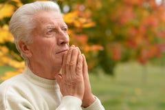 Myślący starszego mężczyzna modlenie Obrazy Stock