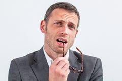 Myślący w średnim wieku biznesmen gryźć jego eyeglasses wyraża wątpliwość Zdjęcia Royalty Free