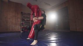 Myśliwska ciupnięcie atrapa uderza pięścią torbę w gym podczas ćwiczyć bojową technikę zbiory