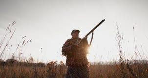 Myśliwy celuje cel z karabinem w polu przy mgłowym rankiem lub pogodnym jesień wieczór zbiory wideo