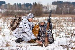 Myśliwy pokazuje jego synów ślada zwierzęta na śnieżnym polu Zdjęcia Royalty Free