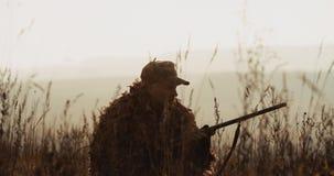 Myśliwy w łowieckim wyposażeniu kłama w czekaniu w polu, celuje cel z strzału pistoletu mgłowym krajobrazem na tle zbiory wideo