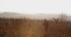 Myśliwy w łowieckim wyposażeniu z karabinem na jego naramiennych spacerach przez pola w słońca światła mgłowym wieczór, las na ho zbiory wideo
