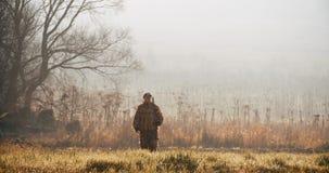 Myśliwy w łowieckim wyposażeniu z karabinem na jego ramieniu chodzi na kamerze w polu przy mgłowym rankiem lub pogodną jesienią zbiory wideo