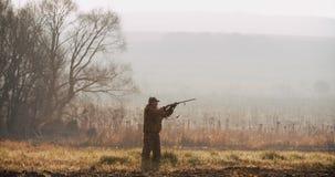 Myśliwy w łowieckim wyposażeniu zobaczył cel z i cel karabinem w śródpolnym mgłowym ranku i lasem na horyzoncie zbiory