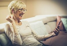My age is not important for laughter and fun. Senior woman at home relaxing with music on phone Royalty Free Stock Image
