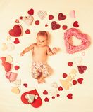 My baby. Family. Child care. Small girl among red hearts. Love. Portrait of happy little child. Childhood happiness
