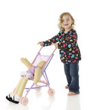 My Baby's Slipping. An adorable preschooler pushing her doll yin an umbrella stroller, but the doll is slipping out.  On a white background Royalty Free Stock Photos