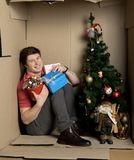 Young man is feeling contentment while holding gifts. My best new year concept. Full length portrait of cheerful guy is sitting on floor ine cramped cardboard Stock Photo