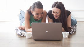 My best University friend forever. Two girls lie on the floor and use the laptop. Smiling and talking to each other stock footage