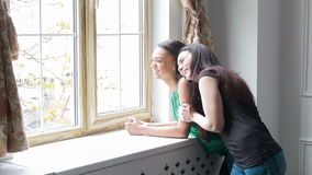 My best University friend forever. Two girls are standing near a window sill and having fun talking to each other. show something in the window and hugging stock footage