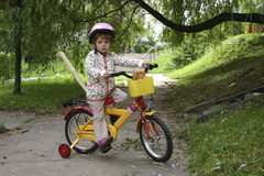 On my bike. Child riding a bike, wearing pink helmet Stock Photography