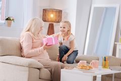 Cheerful elderly woman receiving a present. My birthday. Cheerful nice elderly women sitting on the sofa and feeling happy while receiving a present from her Royalty Free Stock Photos