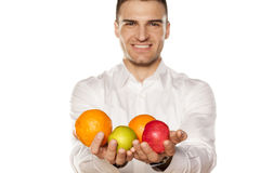 This is my breakfast. Smiling young man, holding handful of fruit in his hands royalty free stock image