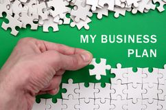 My business plan. The hand folds a white jigsaw puzzle and a pil Royalty Free Stock Photography