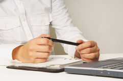 My business plans. Hands holding a pen with a laptop and diary Royalty Free Stock Photo