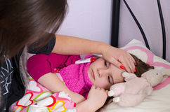 My child girl is sick. Mother taking care about sick daughter Royalty Free Stock Photography