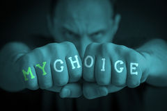 MY CHOICE written on an angry man's fists. MY CHOICE written on the fingers of an angry man's fists. Turquoise colored. Message concept image Stock Photos