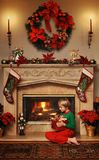 My Christmas gift. 8 year old boy sitting beside the fire with a wrapped Christmas gift in his lap stock photos