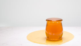 My cup runneth over - a jar overflowing with honey on a white marble countertop Stock Images