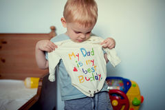 My dad is my best buddy. A child holding a shirt with My dad is my best buddy print royalty free stock images