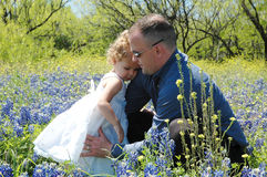My Daddy. A two year old little girl leaning over and hugging her dad in the blue bonnet flowers royalty free stock photography