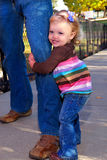My Daddy And Me. An 18 month old toddler girl hugging her daddy's leg as they play in the park royalty free stock photo