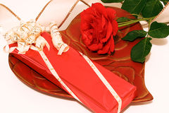For my darling. Rose with gift  and ribbon on a heartplate Royalty Free Stock Photo