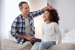 Exuberant daddy caressing his daughter. My darling child. Nice content loving ark-haired men smiling and talking with his daughter and caressing her Royalty Free Stock Photos