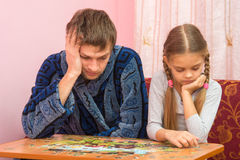 My daughter collects picture from puzzles, tired dad sitting next Royalty Free Stock Photography