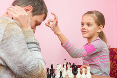 My daughter has a finger on the pope head, who lost a game of chess Stock Photography