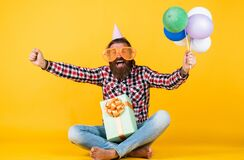 this is my day. man with gift box celebrating birthday. mature hipster with bright colorful balloons. Crazy funny guy
