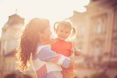 My day with my mom is always full of happiness and glow. Happy mother with her daughter on city street. Close up. Copy space royalty free stock photography