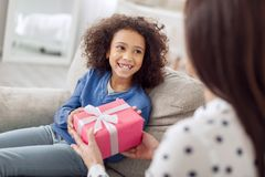 Caring mother giving her daughter a gift. For my dear. Beautiful joyful curly-haired girl sitting on the sofa and smiling and her mother giving her a gift Stock Photo