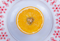 My dear. Orange half and a small heart Royalty Free Stock Image