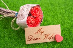 My dear wife. In card with heart and bouquet on grass royalty free stock photography
