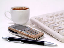 My desk. Pen, cellphone, keyboard, cup on a desk Stock Image