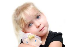 My Doll. Little girl hugging a doll Royalty Free Stock Photography