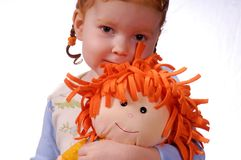 My Dolly. Red haired girl with red haired dolly Royalty Free Stock Photography