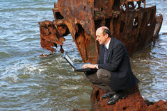 My dream office. Businessman sitting on the rocks at the beach with his laptop and with a beautiful old rusting shipwreck in the background royalty free stock photography