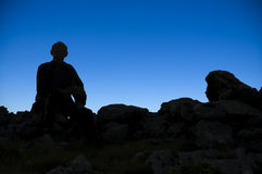 My dreams came true. A man sitting on a top of the mountain watching the sunset Royalty Free Stock Photo