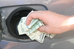 My Earnings. A hand stuffing money into a gas tank Stock Images