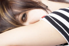 Through my eyes. Close up of a beautiful young woman peaking over her arm with one eye Stock Photography