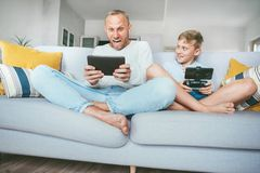 My father funs from PC games just like me.Father and son emotionally playing with electronic devices : tablet and gamepad sitting. In living room royalty free stock photos