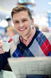 This is my favorite cafe in city. Young man posing at cafe with coffee cup royalty free stock image