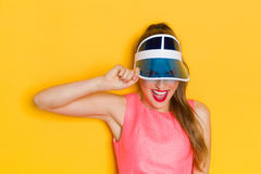 This Is My Favorite Cap. Happy and shouting young woman in pink top looking through transparent blue sun visor. Waist up studio shot on yellow background Royalty Free Stock Photo